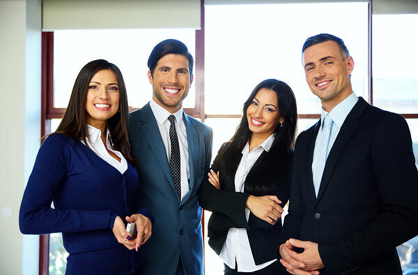Group of cheerful business people standing in office